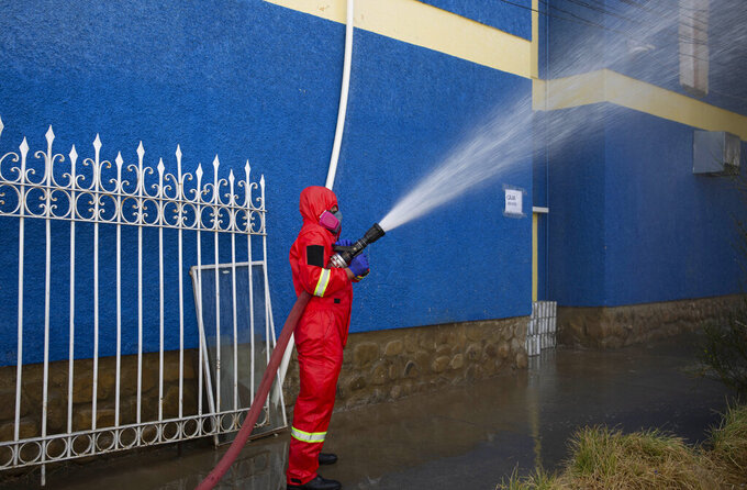 A firefighter disinfects outside the General Hospital in an attempt to contain the spread of the new coronavirus in La Paz, Bolivia, Thursday, July 23, 2020. Police in Bolivia's major cities have recovered the bodies of hundreds of suspected victims of the coronavirus from homes, vehicles, and, in some instances, the streets. (AP Photo/Juan Karita)