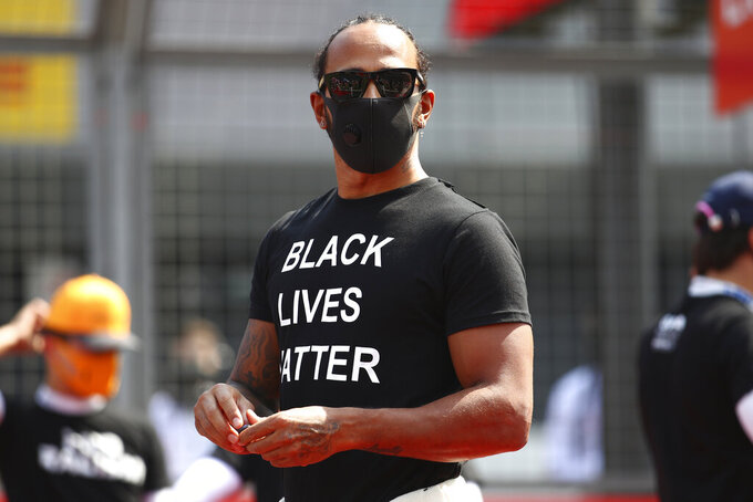 Mercedes driver Lewis Hamilton of Britain, center, wears a face mask ahead of the 70th Anniversary Formula One Grand Prix at the Silverstone circuit, Silverstone, England, Sunday, Aug. 9, 2020. (Bryn Lennon, Pool via AP)