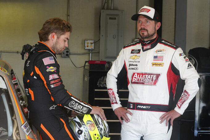 Noah Gragson, left, talks with Michael Annett before practice for the NASCAR Xfinity Series auto race at Indianapolis Motor Speedway, Friday, Aug. 13, 2021, in Indianapolis. (AP Photo/Darron Cummings)