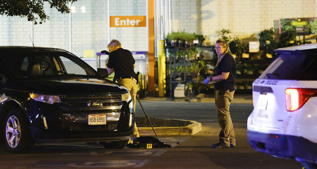 Police investigate the scene after a police officer was shot and killed in the parking lot of a Home Depot in Toledo, Ohio early Saturday, July 4, 2020. (Dave Zapotosky/The Blade via AP)