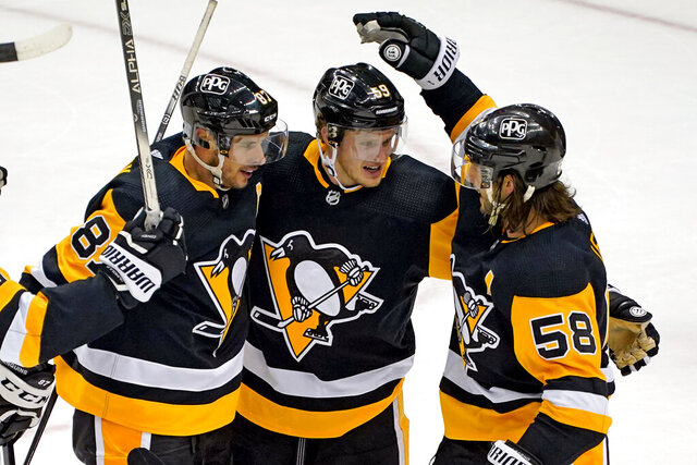 Pittsburgh Penguins' Jake Guentzel (59) celebrates after scoring with Sidney Crosby (87) and Kris Letang during the third period of an NHL hockey game against the New York Rangers in Pittsburgh, Sunday, Jan. 24, 2021. The Penguins won 3-2. (AP Photo/Gene J. Puskar)