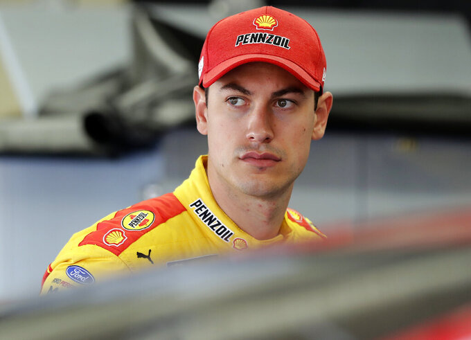 Joey Logano waits to climb into his car before practice for Sunday's NASCAR Cup Series auto race at Charlotte Motor Speedway in Concord, N.C., Saturday, May 25, 2019. (AP Photo/Chuck Burton)