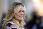 """FILE - In this Oct. 11, 2018, file photo, adult film actress Stormy Daniels attends the opening of the adult entertainment fair 'Venus' in Berlin, Germany. Daniels says she's """"saddened but not shocked"""" over the arrest of her former attorney, Michael Avenatti. Daniels issued a statement Monday, March 25, 2019, on Twitter saying she fired Avenatti a month ago after """"discovering that he had dealt with me extremely dishonestly."""" She said she wouldn't elaborate. Avenatti is best known for representing Daniels in lawsuits against President Donald Trump and has been charged with extortion in New York and bank and wire fraud in California. (AP Photo/Markus Schreiber, File)"""