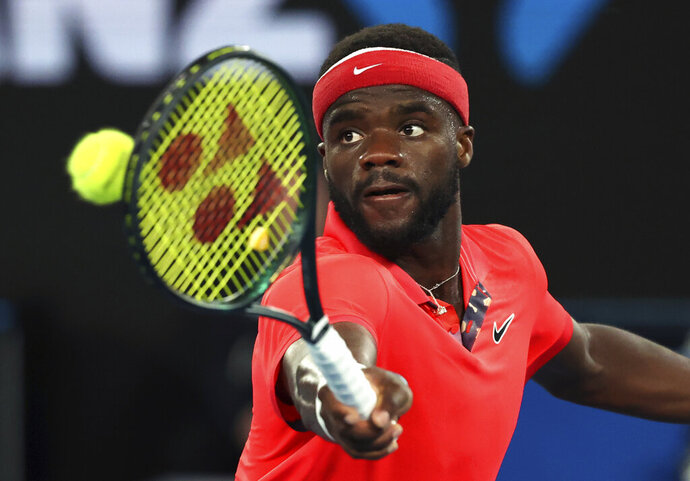 FILE - In this Tuesday, Jan. 21, 2020 file photo, Frances Tiafoe of the United States makes a backhand return to Russia's Daniil Medvedev during their first round singles match at the Australian Open tennis championship in Melbourne, Australia. Frances Tiafoe has tested positive for the coronavirus and withdrawn from the All-American Team Cup tennis tournament. Tiafoe was scheduled to face Tennys Sandgren on Saturday, July 4, 2020 in the weekend tournament involving eight top American men's players at Life Time Fitness in Peachtree Corners.(AP Photo/Lee Jin-man, File)