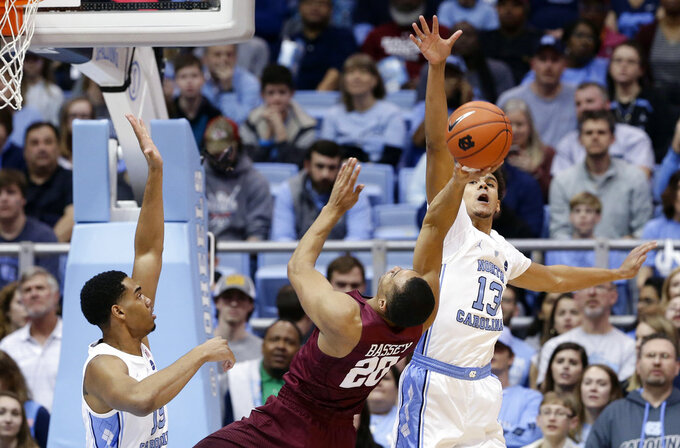 North Carolina's Cameron Johnson (13) and Garrison Brooks, left, defend against Harvard's Justin Bassey (20) during the first half of an NCAA college basketball game in Chapel Hill, N.C., Wednesday, Jan. 2, 2019. (AP Photo/Gerry Broome)