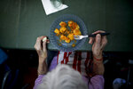 A woman eats lunch at the Reminiscencias residence for the elderly in Tandil, Argentina, Monday, April 5, 2021. Residents here do not have physical contact with their families or leave the residence due to the COVID-19 pandemic, but stay active with group activities within the facility. (AP Photo/Natacha Pisarenko)