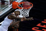 Texas's Kai Jones, top, puts up a shot over Oklahoma State's Kalib Boone during the first half of an NCAA college basketball game for the Big 12 tournament championship in Kansas City, Mo, Saturday, March 13, 2021. (AP Photo/Charlie Riedel)