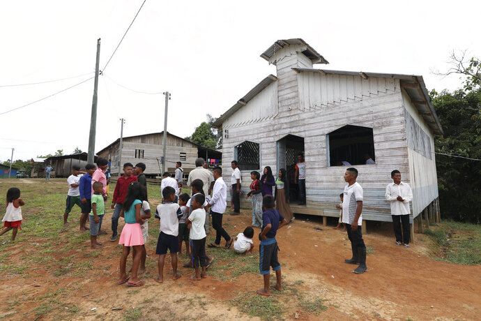 FILE - In this Sept. 22, 2019 file photo, residents gather outside the Catholic church of Novo Cruzador, Brazil, after attending a prayer led by missionary Antelmo Pereira on Sunday, Sept. 22, 2019. Roman Catholic priests, on Wednesday, Feb. 12, 2020, along with deacons and bishops across the Amazon voiced surprise, resignation and reluctant acceptance of Pope Francis' refusal to allow married men to be ordained priests, lamenting that their faithful will continue to be deprived of Mass and subject to competing evangelical churches that have made impressive inroads in the region.  (AP Photo/Fernando Vergara, File)