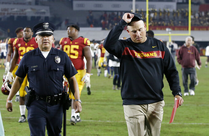 FILE - In this Nov. 10, 2018, file photo, Southern California head coach Clay Helton, right, walks off the field after a loss to California in an NCAA college football game in Los Angeles. With angry USC fans chanting for Helton's firing, the Trojans fell 34-27 to UCLA last week for their fourth loss in five games. Ranked 15th at the start of the season, USC (5-6) now must upset Notre Dame on Saturday just to become bowl eligible and avoid its first seven-loss regular season since 2000. (AP Photo/Alex Gallardo, File)