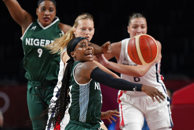 Nigeria's Ezinne Kalu, center, loses control of the ball as she is fouled by France's Marine Johannes during a women's basketball game at the 2020 Summer Olympics, Friday, July 30, 2021, in Saitama, Japan. (AP Photo/Eric Gay)