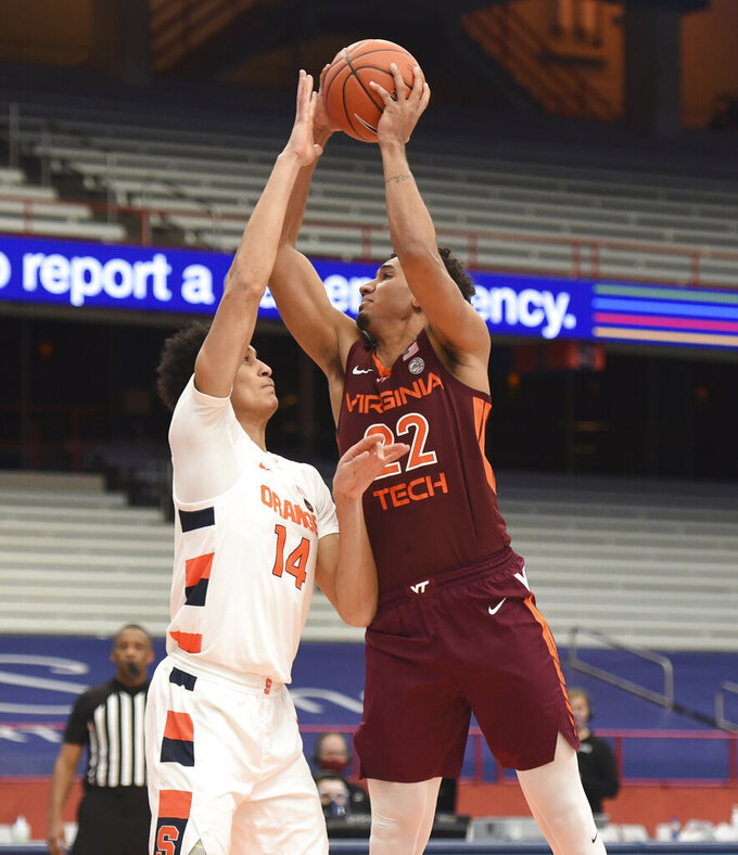 Virginia Tech forward Keve Aluma (22) put up a shot against Syracuse center Jesse Edwards (14) during an NCAA college basketball game at the Carrier Dome, Syracuse, N.Y., Saturday Jan. 23, 2021. (Scott Schild/The Post-Standard via AP)