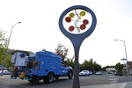 A Pacific Gas & Electric truck drives on Moraga Way as a decorative wind spinner sits motionless in Orinda, Calif., on Thursday, Oct. 10, 2019. Business continue to be closed due to the recent PG&E shutdown. The utility company began restoring power to Bay Area residents Thursday, taking the first steps in what could be a days-long process to end an outage that left many homes and businesses in the dark. (Jose Carlos Fajardo/East Bay Times via AP)