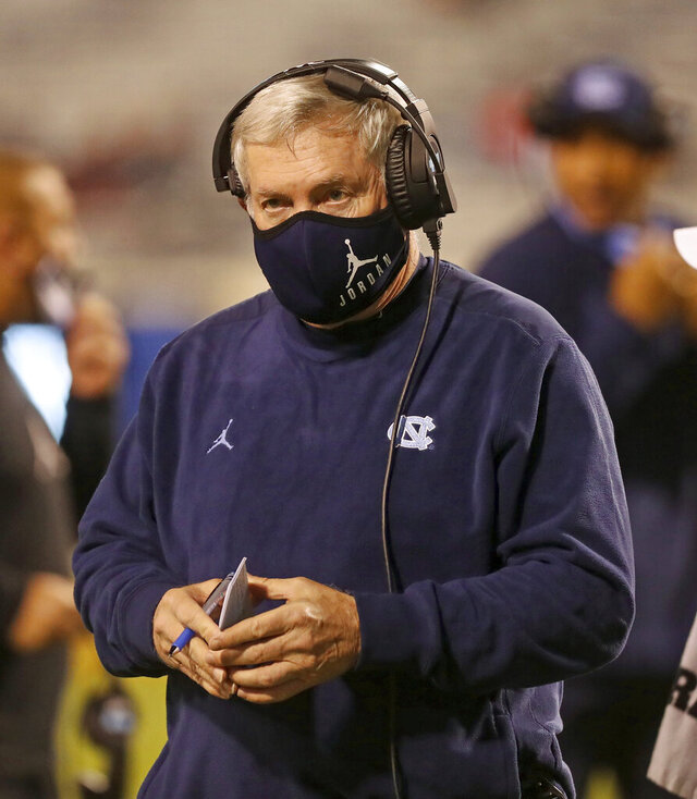 """FILE - In this Oct. 31, 2020, file photo, North Carolina coach Mack Brown watches a play during the team's NCAA college football game against Virginia, in Charlottesville, Va. The ACC hosted a Mental Health and Wellness Summit in 2019 in Durham, North Carolina. A second one was planned for last May before being scuttled by the pandemic. """"Many years ago, we didn't say much about it (mental health) at all,"""" North Carolina coach Mack Brown said. Now, it's a frequent topic. (Andrew Shurtleff/The Daily Progress via AP, File)"""