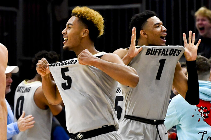 Colorado guard D'Shawn Schwartz (5) and guard Tyler Bey (1) react after the team defeated Dayton 78-76 in overtime in an NCAA college basketball game, Saturday, Dec. 21, 2019, in Chicago. (AP Photo/Matt Marton)