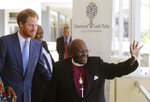 FILE - In this Monday, Nov. 30, 2015, file photo Britain's Prince Harry, left, looks on as South African Archbishop Desmond Tutu waves at people during his visit to The Desmond and Leah Tutu Legacy Foundation in Cape Town, South Africa. Prince Harry and his wife, Meghan, along with their infant son, Archie, are making their first official tour as a family, starting Monday and will visit meet with the Tutus. (AP Photo/Schalk van Zuydam, File)
