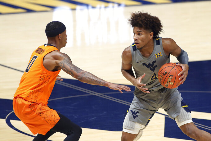 West Virginia guard Miles McBride (4) is defended by Oklahoma State guard Avery Anderson III (0) during the second half of an NCAA college basketball game Saturday, March 6, 2021, in Morgantown, W.Va. (AP Photo/Kathleen Batten)
