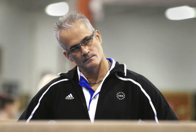 John Geddert watches his students during practice in December 2011. Geddert, a former U.S. Olympics gymnastics coach with ties to disgraced sports doctor Larry Nassar, killed himself Thursday, Feb. 25, 2021, hours after being charged with turning his Michigan gym into a hub of human trafficking by coercing girls to train and then abusing them. Geddert faced 24 charges that could have carried years in prison had he been convicted. (Greg DeRuiter/Lansing State Journal via AP)