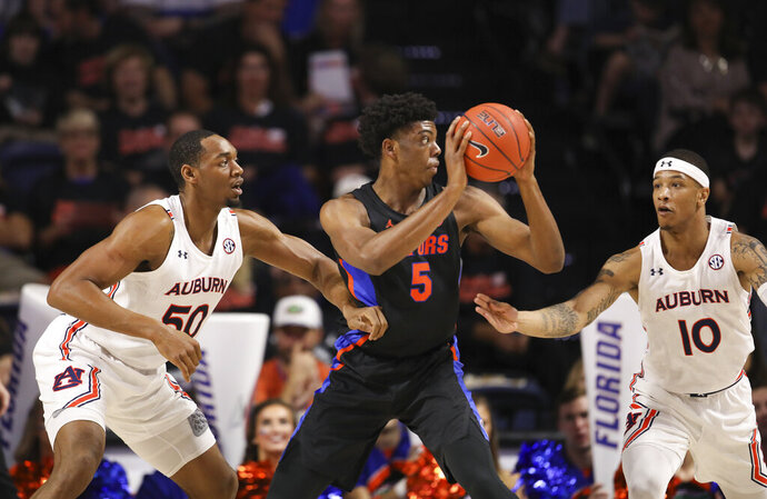 Florida forward Omar Payne (5) spins between Auburn center Austin Wiley (50) and guard Samir Doughty (10) during the first half of an NCAA college basketball game Saturday, Jan. 18, 2020, in Gainesville, Fla. (AP Photo/Matt Stamey)