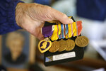 Don Long pulls out his Purple Heart and other medals at his home Friday, Dec. 7, 2018, in Napa, Calif., before driving to attend a number of Pearl Harbor remembrances. Retired U.S. Navy Cmdr. Don Long wasn't at Pearl Harbor when Japanese war planes started bombing Hawaii on December 7, 1941, he was on the opposite side of Oahu standing watch aboard an anchored military seaplane in Kaneohe Bay. But the wave of bombs and bullets reached his military installation soon after Pearl Harbor was struck, and the young sailor watched from afar as buildings and planes started to explode all around him. On the 77th anniversary of the attack, Long will remember from his home where the 97-year-old survivor will reflect and honor those who died. (AP Photo/Eric Risberg)