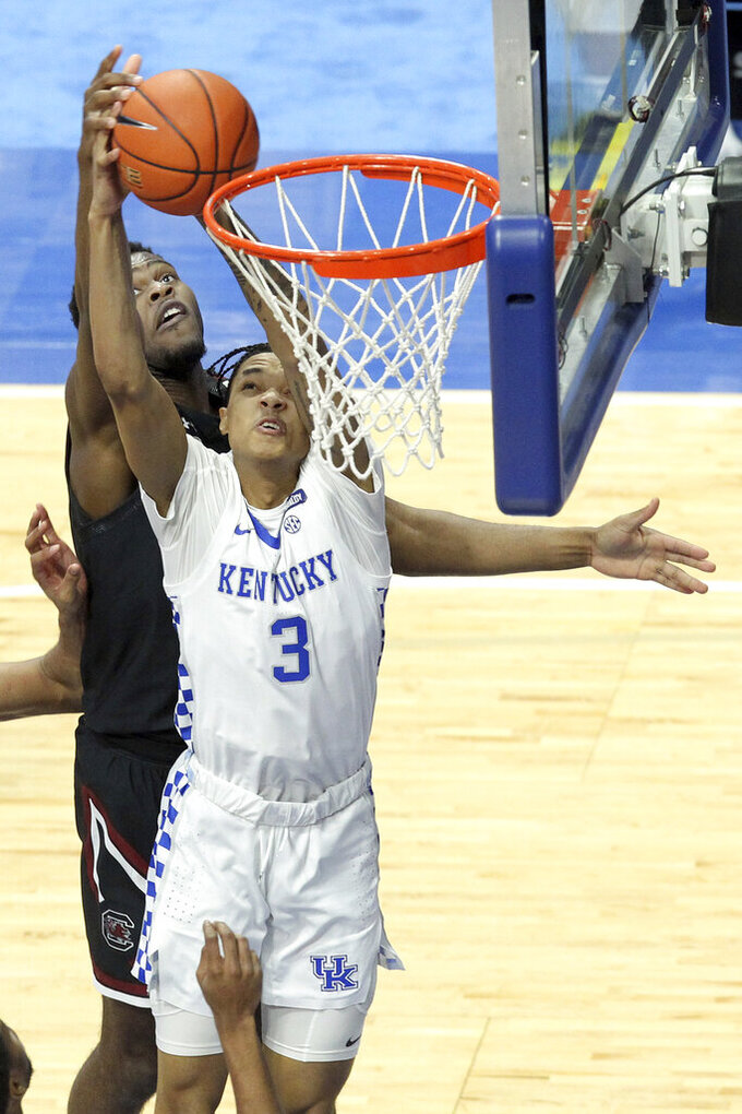Kentucky's B.J. Boston (3) is fouled from behind by South Carolina's Wildens Leveque while going for a rebound during the first half of an NCAA college basketball game in Lexington, Ky., Saturday, March 6, 2021. (AP Photo/James Crisp)