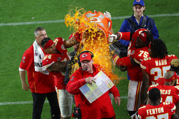 Kansas City Chiefs outside linebacker Damien Wilson (54), tight end Travis Kelce (87) and offensive tackle Cameron Erving (75) douse head coach Andy Reid with Gatorade in celebration of a victory during the NFL Super Bowl football game against the Kansas City Chiefs, Sunday, Feb. 2, 2020 in Miami Gardens, Fla. The Chiefs defeated the 49ers 31-20.(Margaret Bowles via AP)