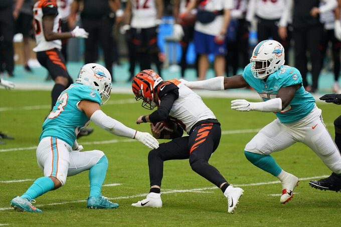 Miami Dolphins offensive guard Michael Deiter (63), left, and defensive end Jason Strowbridge (58) tackle Cincinnati Bengals quarterback Brandon Allen (8), during the first half of an NFL football game, Sunday, Dec. 6, 2020, in Miami Gardens, Fla. (AP Photo/Wilfredo Lee)