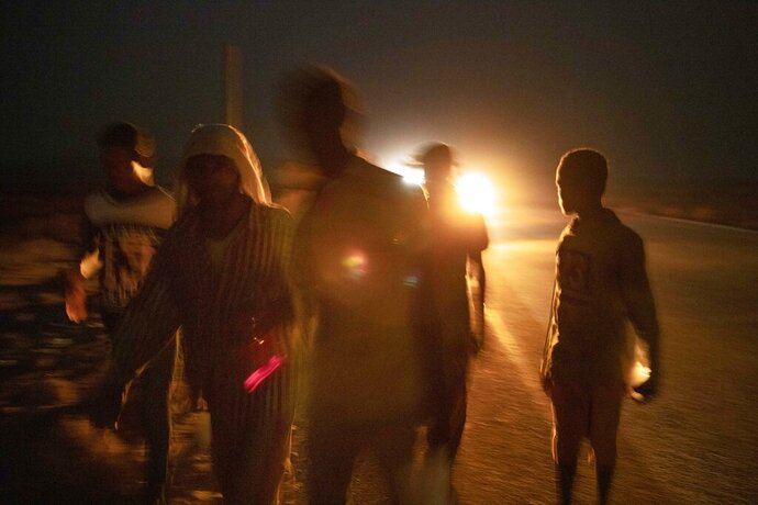 In this July 12, 2019 photo, 35-year-old Mohammed Eissa, second left, walks on a highway with boys he met on the way, around 50 kilometers (31 miles) from Djibouti. Eissa had left behind his wife, nine sons and a daughter. His wife cares for his elderly father. The children work the farm growing vegetables, but harvests are unpredictable: