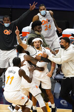 Orlando Magic's Cole Anthony, center with extended hand, is mobbed by teammates after his game-winning, 3-point basket against the Minnesota Timberwolves at the ending buzzer of an NBA basketball game, Wednesday, Jan. 20, 2021, in Minneapolis. The Magic won 97-96. (AP Photo/Jim Mone)