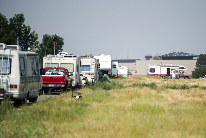A row of RV's are parked along Patrick Street on Friday, July 30, 2021, in Bozeman, Mont. The tight market has pushed some in the city to give up living in a stationary home and become full-time residents of their RVs, campers or trailers. Small cities of all varieties of motor homes have popped up in local campgrounds, big-box store parking lots and side streets. (Rachel Leathe/Bozeman Daily Chronicle via AP)