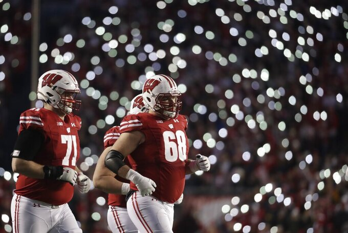 Wisconsin's David Moorman and Cole Van Lanen take the field during the second half of an NCAA college football game against Iowa Saturday, Nov. 9, 2019, in Madison, Wis. Wisconsin won 24-22. (AP Photo/Morry Gash)