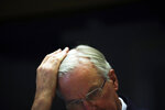 European Union chief Brexit negotiator Michel Barnier combs his hair as he attends a debate on post-Brexit relations with United Kingdom at the European Parliament in Brussels, Wednesday, Oct. 30, 2019. A respected British think tank slammed Prime Minister Boris Johnson's Brexit deal on Wednesday, concluding that the economy would be 3.5% smaller over the next decade compared with staying in the European Union. (AP Photo/Francisco Seco)