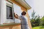 Wendell Smith unfolds his storm shutters over a window on his Arden Forest home in preparation for the arrival of Hurricane Isaias, in Freeport, Grand Bahama, Bahamas, Friday, July 31, 2020. (AP Photo/Tim Aylen)
