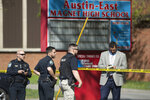 Law enforcement officers respond to a shooting at Austin-East Magnet High School in Knoxville, Tenn., Monday, April 12, 2021. Authorities say multiple people including a police officer have been shot at the school. (Saul Young/Knoxville News Sentinel via AP)