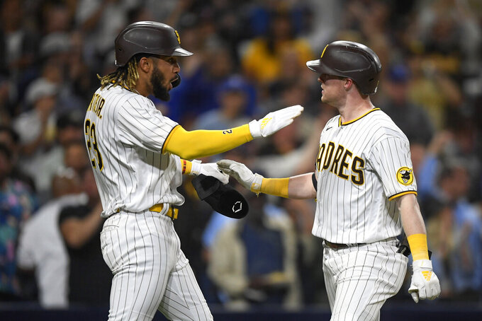 San Diego Padres' Jake Cronenworth, right, is congratulated by Fernando Tatis Jr. after Cronenworth hit a two-run home run in the fifth inning of a baseball game against the Los Angeles Dodgers, Monday, June 21, 2021, in San Diego. (AP Photo/Denis Poroy)
