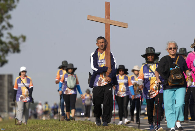 Pilgrims walk on the shoulder of a highway toward Our Lady of Aparecida Basilica on the outskirts of Aparecida, Brazil, Monday, Oct. 12, 2020. Two of Brazil's biggest Catholic celebrations scheduled for this holiday weekend were downscaled and canceled, yet people still appeared in droves, underscoring the challenge of extolling COVID-19 precautions as well as pressures to ease up. (AP Photo/Andre Penner)