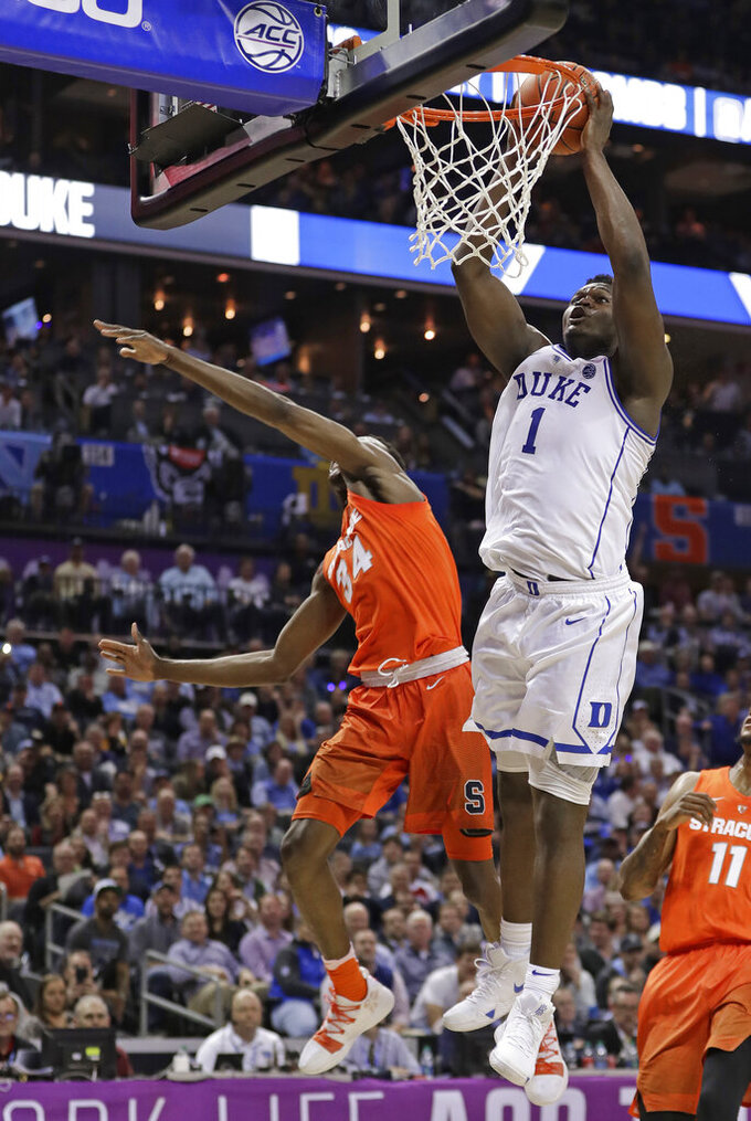 Duke's Zion Williamson (1) dunks past Syracuse's Bourama Sidibe (34) during the first half of an NCAA college basketball game in the Atlantic Coast Conference tournament in Charlotte, N.C., Thursday, March 14, 2019. (AP Photo/Nell Redmond)