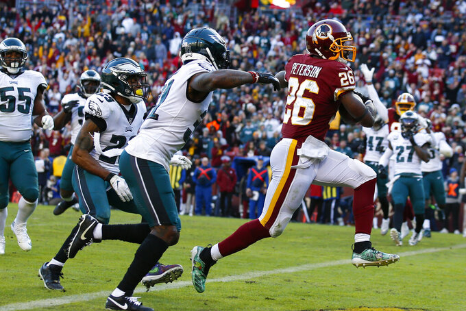 Washington Redskins running back Adrian Peterson (26) runs past Philadelphia Eagles free safety Rodney McLeod (23) and cornerback Jalen Mills (31) to score a touchdown in the second half of an NFL football game, Sunday, Dec. 15, 2019, in Landover, Md. (AP Photo/Alex Brandon)