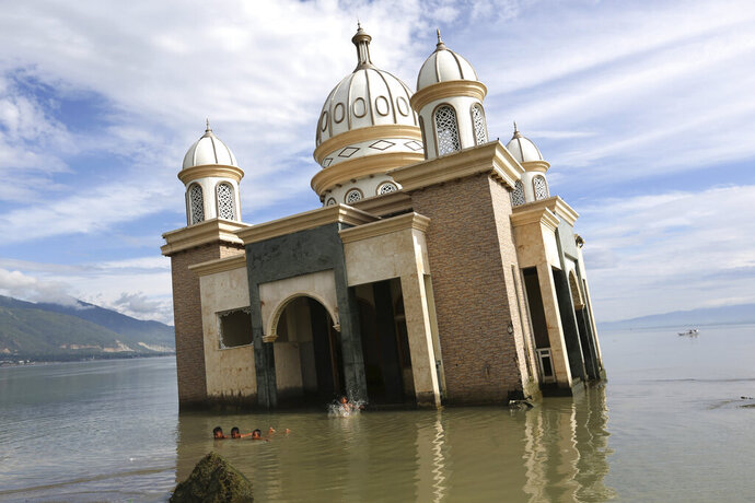 In this Wednesday, April 3, 2019, photo, children play in the water on a beach near a mosque collapsed during Sept. 28, 2018, earthquake is seen in the background in Palu, Central Sulawesi, Indonesia. The earthquake spawned a large localized tsunami that wiped out coastal areas, while liquefaction caused by the shaking turned entire neighborhoods into rivers of sludge. The disaster killed thousands of people, making it the world's deadliest seismic event in 2018. (AP Photo/Tatan Syuflana)