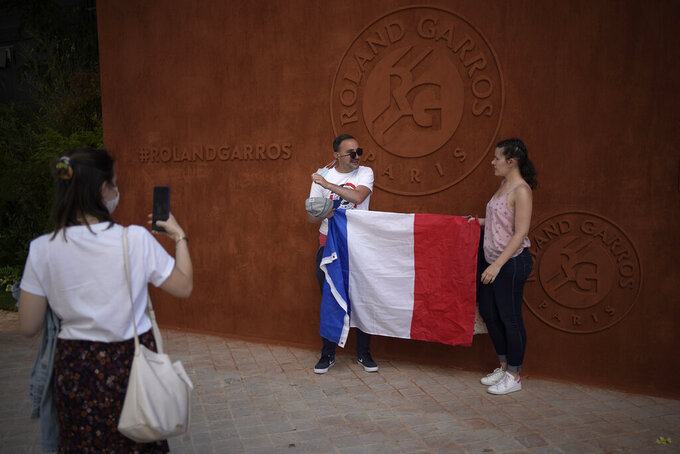 Tennis lovers pose with a French flag at the Roland Garros stadium during their first round of the French Open tennis tournament Sunday, May 30, 2021 in Paris. (AP Photo/Christophe Ena)