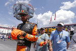 Driver Martin Truex Jr. signs autographs as he walks through the pits before practice for a NASCAR Cup Series auto race, Friday, Aug. 16, 2019, in Bristol, Tenn. (AP Photo/Wade Payne)