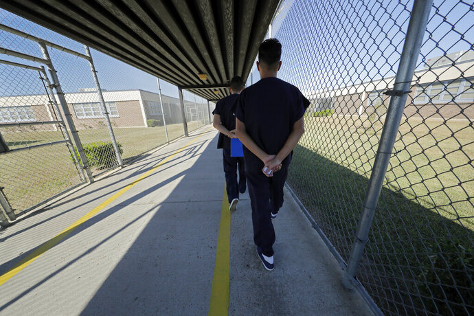 FILE - In a Thursday, Sept. 26, 2019 file photo, detainees walk with their hands clasped behind their backs along a line painted on a walkway inside the Winn Correctional Center in Winnfield, La. Asylum seekers detained at an immigration jail in northern Louisiana are refusing to move into their cells in what their families say is a protest of their prolonged detention. U.S. Immigration and Customs Enforcement confirmed Tuesday, Dec. 2 that there is an ongoing protest at the Winn Correctional Center in rural Winnfield. (AP Photo/Gerald Herbert, File)