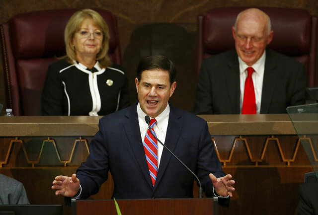 FILE - In this Jan. 14, 2019, file photo, Arizona Republican Gov. Doug Ducey speaks during his state of the state address as he talks about Arizona's economy, new jobs, and the state revenue as Senate president Karen Fann, R-Prescott, left, and House Speaker Rusty Bowers, R-Mesa, right, listen in Phoenix. Ducey appears supremely confident in the direction he's set for the state as he heads into his sixth year in office and prepares to present his annual State of the State address Monday, Jan. 11, 2020. (AP Photo/Ross D. Franklin, File)