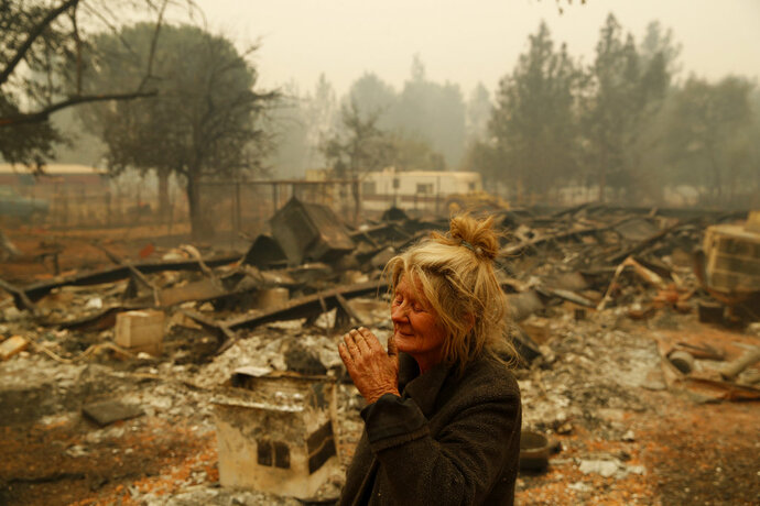 Cathy Fallon reacts as she stands near the charred remains of her home, Friday, Nov. 9, 2018, in Paradise, Calif.