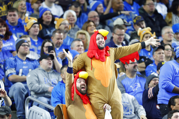 Football fans dressed as turkeys cheer during the first half of an NFL football game between the Detroit Lions and the Chicago Bears, Thursday, Nov. 28, 2019, in Detroit. (AP Photo/Paul Sancya)