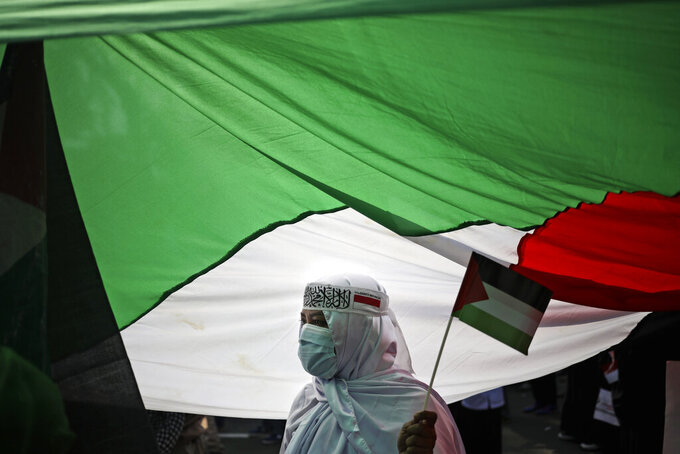 A protester stands under a large Palestinian flag during an anti-Israel rally outside the U.S. Embassy in Jakarta, Indonesia, Tuesday, May 18, 2021. Pro-Palestinian protesters marched to the heavily guarded embassy on Tuesday to demand an end to Israeli airstrikes in the Gaza Strip. (AP Photo/Dita Alangkara)