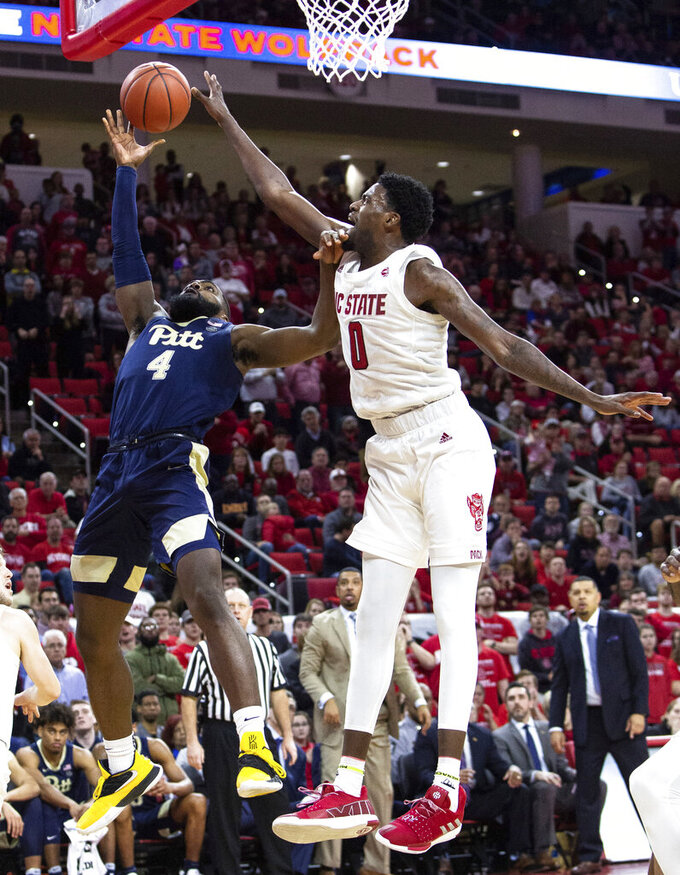 Pittsburgh's Jared Wilson-Frame (4) attempts a shot over North Carolina State's DJ Funderburk (0) during the second half of an NCAA college basketball game in Raleigh, N.C., Saturday, Jan. 12, 2019. (AP Photo/Ben McKeown)
