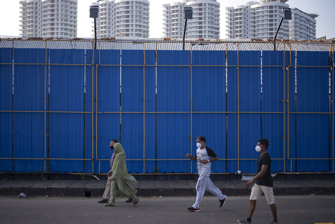 People wearing masks as a precaution against the coronavirus take a morning walk past a high-rise residential complex in Kochi, Kerala state, India, Friday, Nov. 20, 2020. India's total number of coronavirus cases since the pandemic began crossed 9 million on Friday. (AP Photo/R S Iyer)