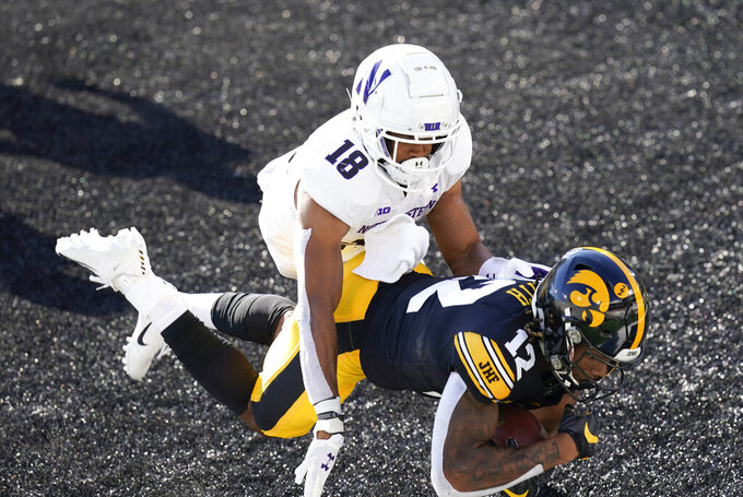 Iowa wide receiver Brandon Smith (12) catches a 7-yard touchdown pass ahead of Northwestern defensive back Cameron Ruiz (18) during the first half of an NCAA college football game, Saturday, Oct. 31, 2020, in Iowa City, Iowa. (AP Photo/Charlie Neibergall)