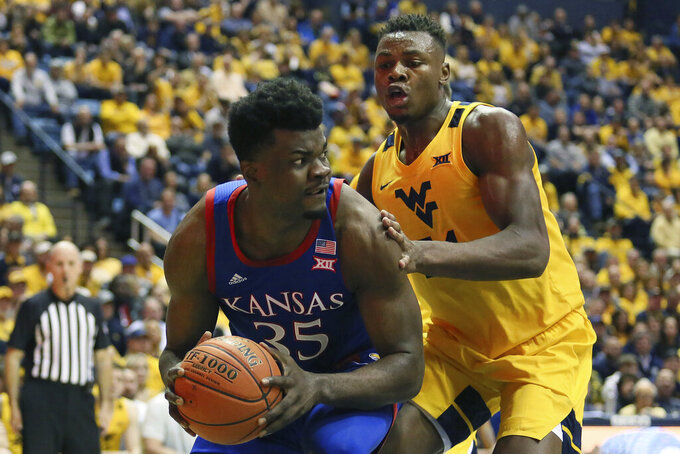 FILE - Kansas center Udoka Azubuike (35) is defended by West Virginia forward Oscar Tshiebwe (34) during the first half of an NCAA college basketball game in Morgantown, W.Va., in this Wednesday, Feb. 12, 2020, file photo. West Virginia opens the 2020-21 season ranked No. 15 in the AP poll and returns four of the top five scorers from the team that went 21-10 last season. (AP Photo/Kathleen Batten, File)