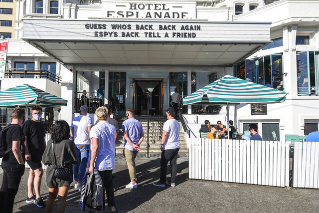 People line up outside a popular pub and restaurant in St Kilda in Melbourne, Australia, Wednesday, Oct. 28, 2020. Melbourne, Australia's former coronavirus hot spot, emerged from a lockdown at midnight Tuesday, restaurants, cafes and bars were allowed to open and outdoor contact sports can resume. (AP Photo/Asanka Brendon Ratnayake)